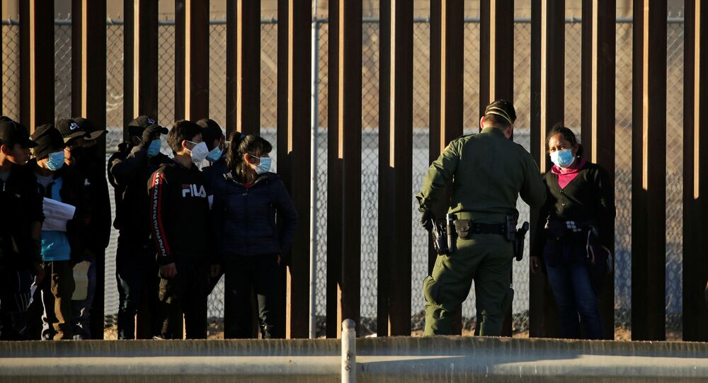 Migrants from Central America are detained by a U.S. Border Patrol agent as they turn themselves in to request asylum, after crossing into El Paso, Texas, U.S., as seen from Ciudad Juarez, Mexico January 22, 2021