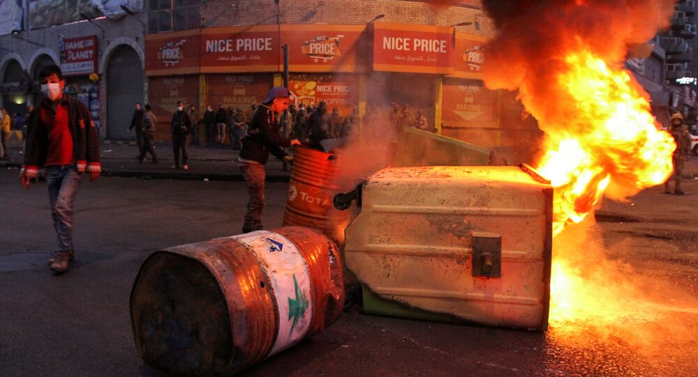 Garbage bins, set on fire by demonstrators, block a road during a protest against the lockdown and worsening economic conditions, amid the spread of the coronavirus disease (COVID-19), in Tripoli, Lebanon January 26, 2021. REUTERS/Omar Ibrahim