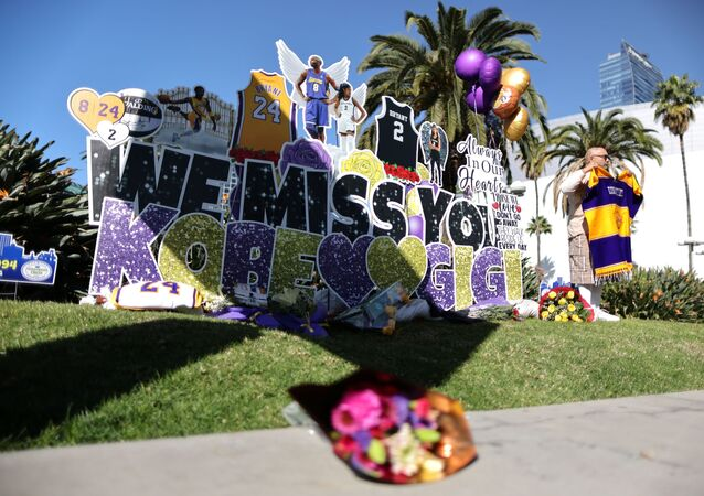 Flowers and pictures are placed as fans gather for a memorial to late Kobe Bryant, who perished one year ago alongside his daughter and seven others when their helicopter crashed into a hillside near Los Angeles, outside the Staples Center in Los Angeles, California, U.S., January 26, 2021