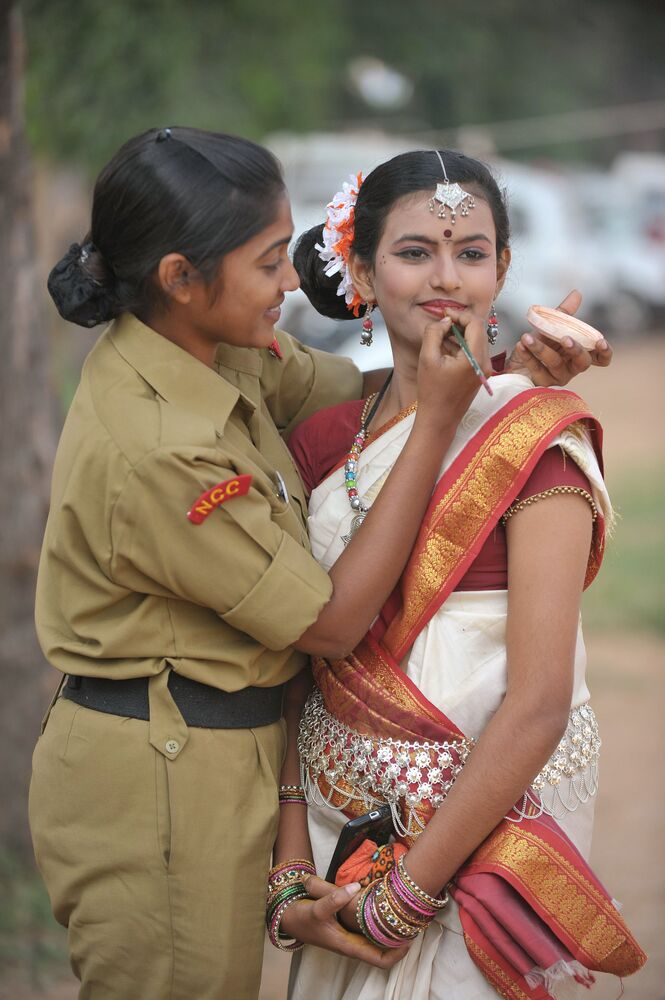 An Indian National Cadet Corps (NCC) member gives the final touch up to her colleagues makeup prior to performing in a cultural programme during the 66th NCC day celebrations in Secunderabad, the twin city of Hyderabad on 22 November 2014.