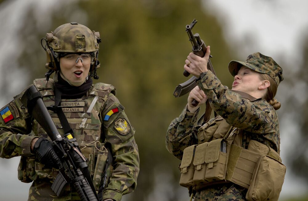 A Romanian female soldier, left, and a US Marines female counterpart share a joke after switching weapons to get usedto each other's equipment during training at the Capu Midia surface-to-air firing range, on the Black Sea coast in Romania, 20 March 2017.