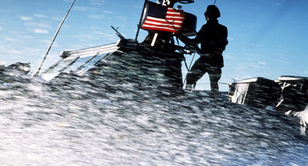 Spray from the bow of a Seafox special warfare patrol craft from Special Boat Unit 12 obscures Sea-Air-Land (SEAL) team members standing on the deck during an exercise