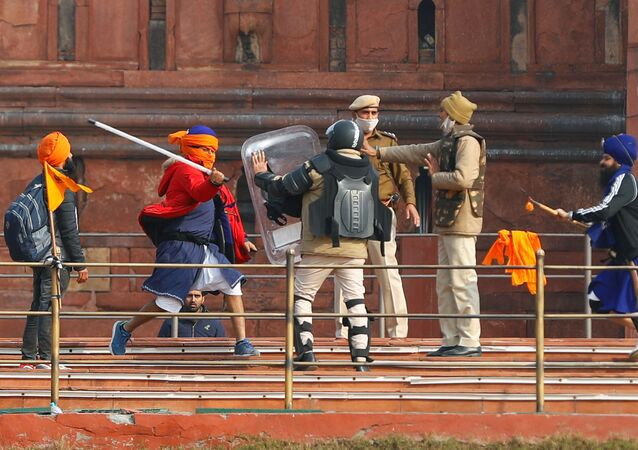 A Nihang (sikh warrior) beats a policeman with a baton during a protest against farm laws introduced by the government, at the historic Red Fort in Delhi, India, 26 January 2021.