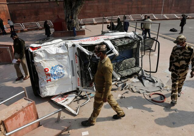 Policemen walk past a damaged police vehicle outside the historic Red Fort after Tuesday's clashes between police and farmers, in the old quarters of Delhi, India, January 27, 2021