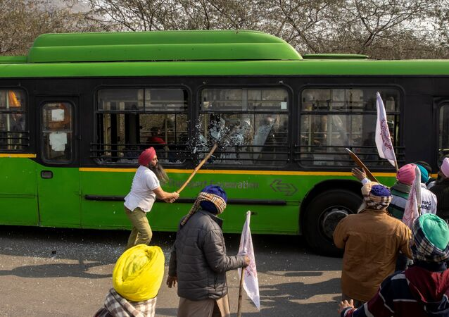 A farmer breaks windows of a government bus as during a tractor rally to protest against farm laws on the occasion of India's Republic Day in New Delhi, India, 26 January 2021.