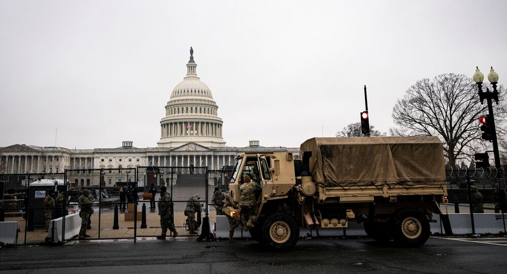 U.S. National Guard troops unload food near barbed wire and security fencing around the U.S. Capitol in Washington, U.S., January 26, 2021. REUTERS/Al Drago