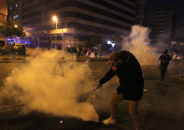 A demonstrator extinguishes a tear gas during a protest against the lockdown and worsening economic conditions, amid the spread of the coronavirus disease (COVID-19), in Tripoli, Lebanon January 27, 2021. REUTERS/Omar Ibrahim