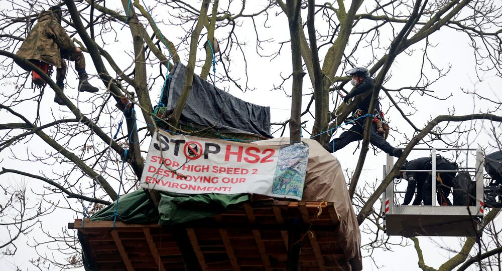 Enforcement agents use a cherry picker to reach an Extinction Rebellion activist who demonstrates on a tree as others occupy tunnels under Euston Square Gardens, to protest against the HS2 high-speed railway in London, Britain, January 27, 2021
