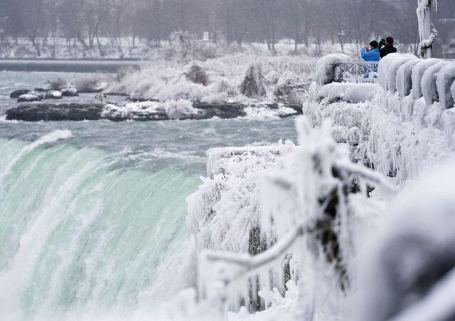 Two men take photographs at the Horseshoe Falls in Niagara Falls, Ontario, on 27 January 2021.