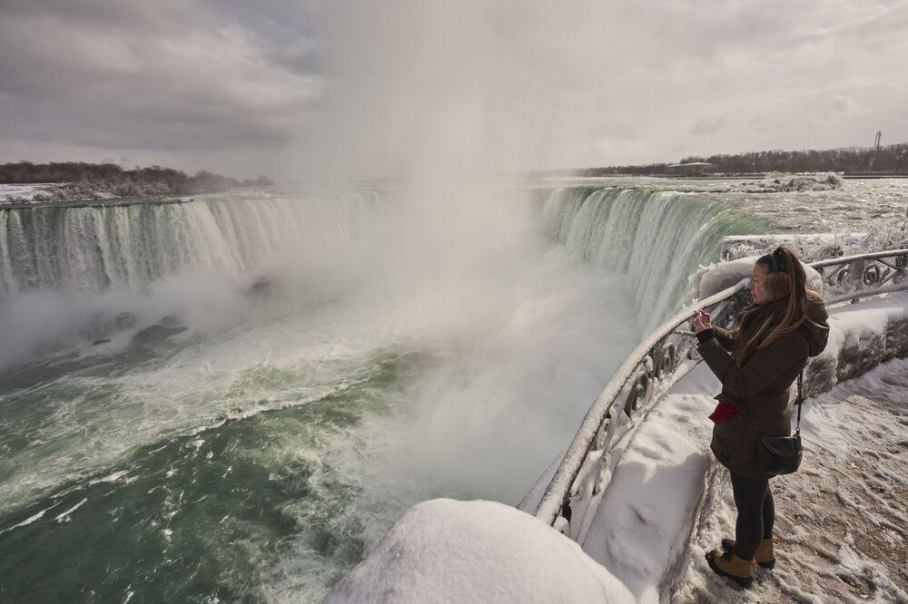 A woman takes a photo at the Horseshoe Falls in Niagara Falls, Ontario, on 27 January 2021.
