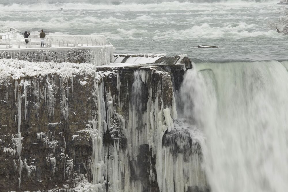 A person has their photo taken on the US side of the Horseshoe Falls in Niagara Falls, New York, on 27 January 2021, as taken from the Canadian side.