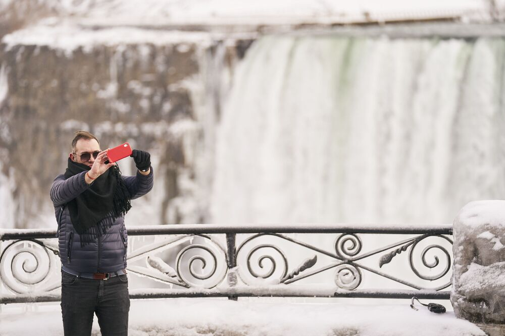 A man takes a selfie in front of the Horseshoe Falls in Niagara Falls, Ontario, on 27 January 2021.