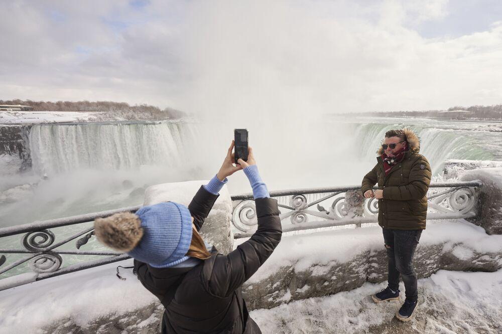 A man has his photo taken at the Horseshoe Falls in Niagara Falls, Ontario, on 27 January 2021.