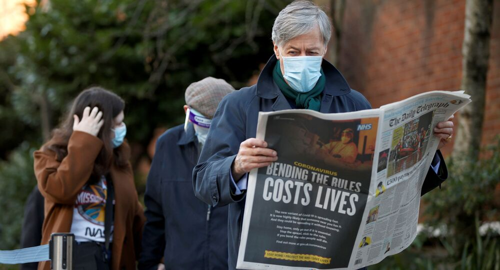 A man reads a newspaper as he waits to enter Lord's Cricket Ground to receive the coronavirus vaccine, amid the outbreak of the coronavirus disease (COVID-19), in London, UK, 22 January 2021.