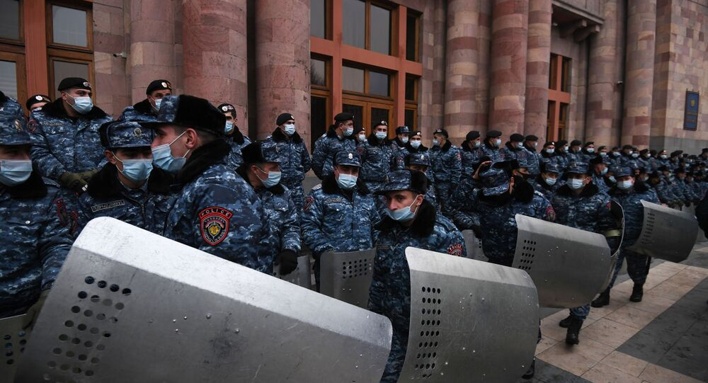 Police officers wear protective face masks during a rally demanding the resignation of Prime Minister Nikol Pashinyan, at Republic Square, in Yerevan, Armenia.