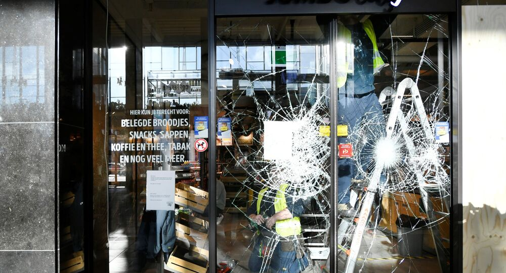 Glaziers remove broken glass at a supermarket after yesterday's riots against the COVID-19 lockdown in Eindhoven, Netherlands January 25, 2021.