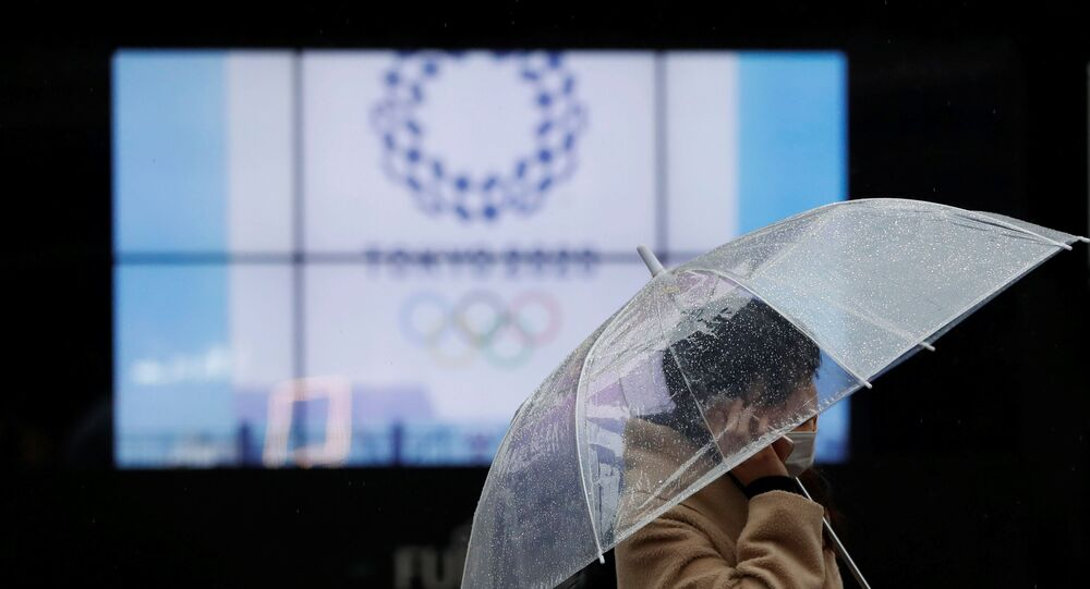 A passerby wearing a protective face mask walks past a display showing the logo of Tokyo 2020 Olympic Games that have been postponed to 2021 due to the coronavirus disease (COVID-19) outbreak, in Tokyo, Japan January 23, 2021.