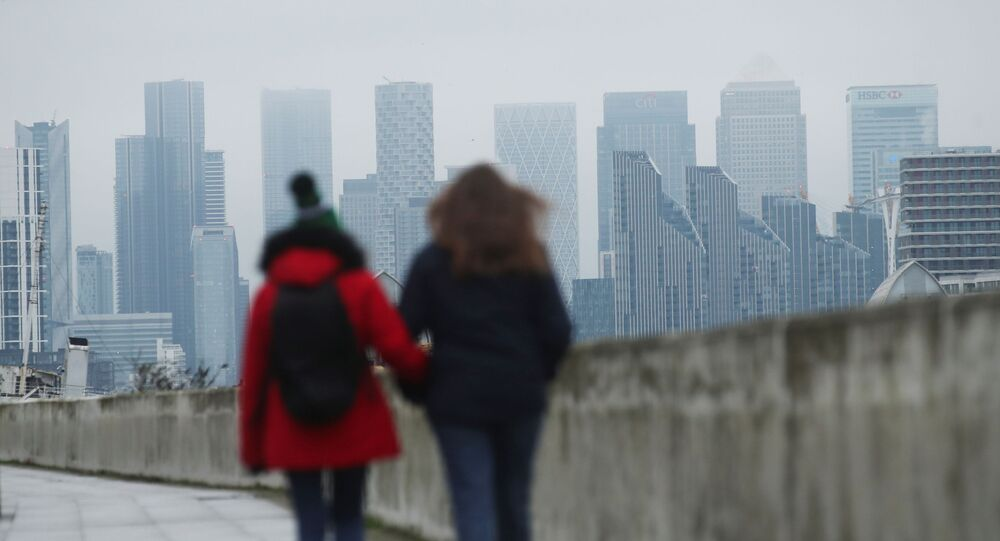 Buildings are seen in the Canary Wharf business district, as people walk along a footpath, amid the outbreak of the coronavirus disease (COVID-19), in London, Britain January 27, 2021.