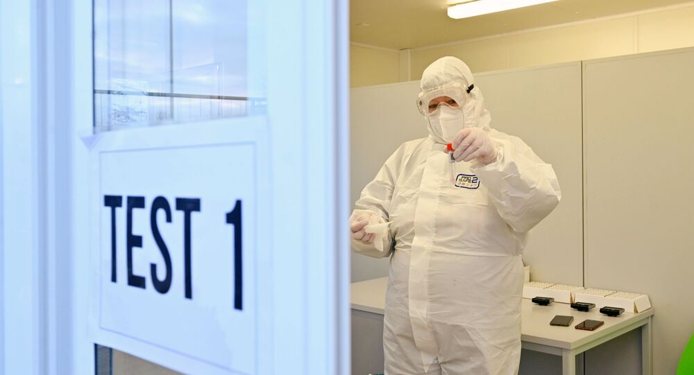A medical worker controls a solution with a smear from a tested person in a quick test center, amid the coronavirus disease (COVID-19) pandemic, in Kodersdorf, Germany January 25, 2021. REUTERS/Matthias Rietschel