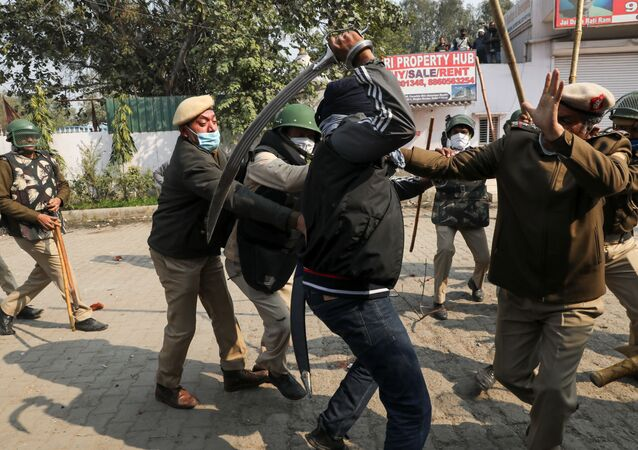 A man wields his sword against a policeman during a clash between protesting farmers and a group of people shouting anti-farmer slogans, at a site of the protest against farm laws at Singhu border near New Delhi, India January 29, 2021.