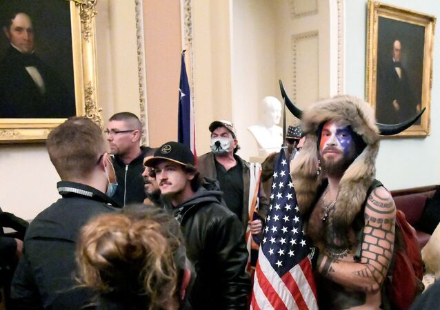Jacob Anthony Chansley, also known as Jake Angeli, of Arizona, stands with other supporters of U.S. President Donald Trump as they demonstrate on the second floor of the U.S. Capitol near the entrance to the Senate after breaching security defenses, in Washington, U.S., January 6, 2021.