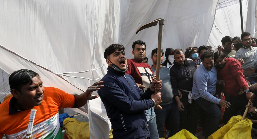 A man, from the group which raised the anti-farmers slogan, shouts as he holds a scythe, at a site of the protest against farm laws at Singhu border near New Delhi, India January 29, 2021. REUTERS/Anushree Fadnavis