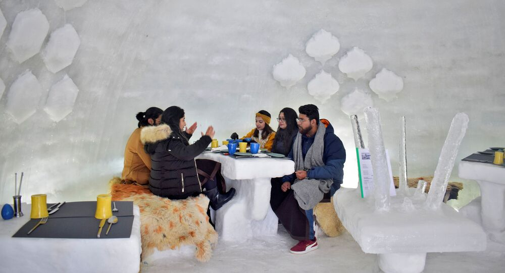 Tourists drink inside Igloo Cafe, a cafe prepared with snow and ice, at Gulmarg, a ski resort and one of the main tourist attractions in Kashmir region, January 28, 2021