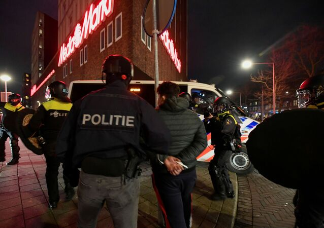 Police officers detain a demonstrator protesting against restrictions put in place to curb the spread of the coronavirus disease (COVID-19) in Rotterdam, Netherlands, January 26, 2021.