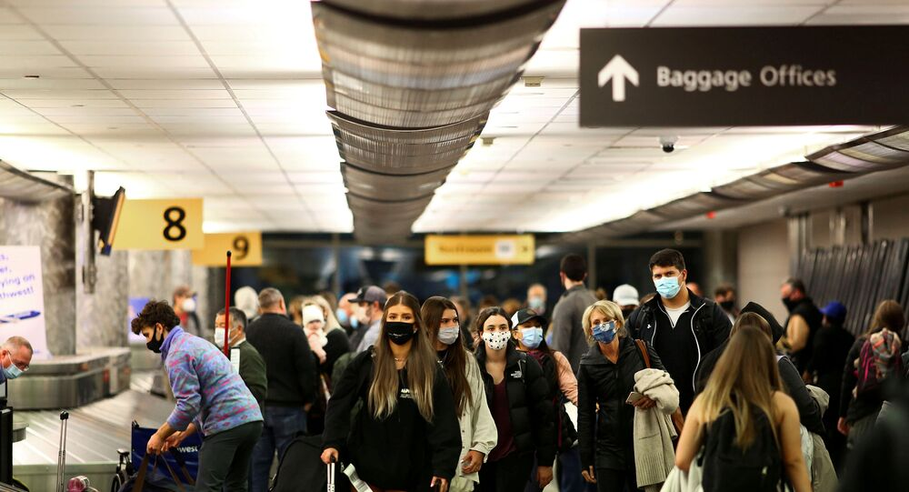 Travelers wearing protective face masks to prevent the spread of the coronavirus disease (COVID-19) reclaim their luggage at the airport in Denver, Colorado, U.S., November 24, 2020.