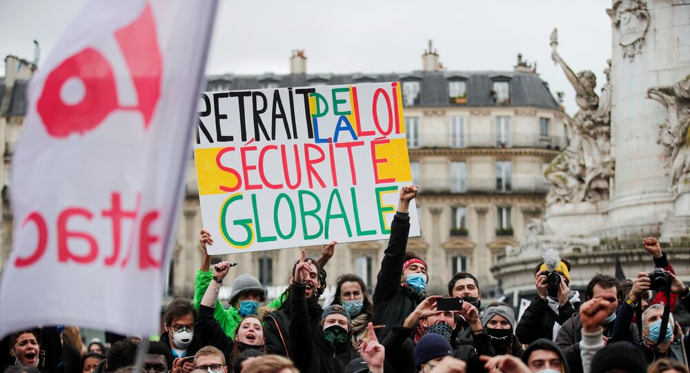 A person holds a placard reading ''withdrawal of the global security law'' during demonstration against the Global Security Bill'', that right groups say would make it a crime to circulate an image of a police officer's face and would infringe journalists' freedom in the country, in Paris, France, January 30, 2021. REUTERS/Benoit Tessier