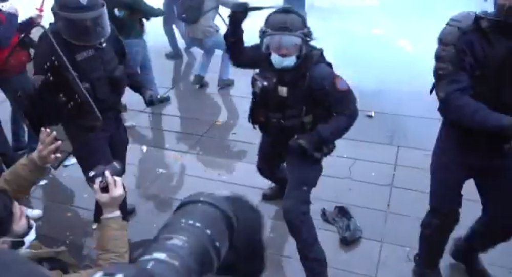 Screenshot from a video showing a police officer in Paris using his baton against a protester