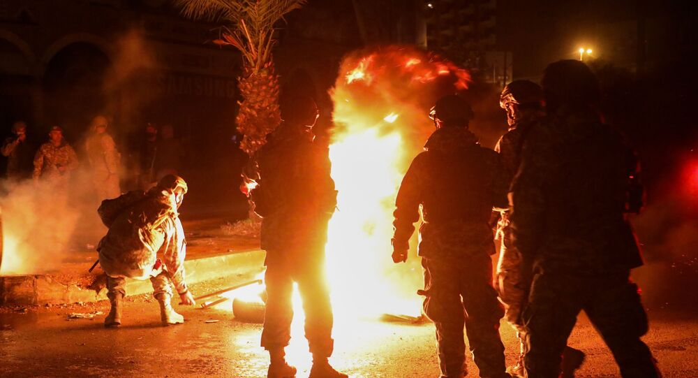 Members of the Lebanese army stand near burning tires during a protest against the lockdown and worsening economic conditions, amid the spread of the coronavirus disease (COVID-19), in Tripoli, Lebanon January 29, 2021. REUTERS/Mohamed Azakir