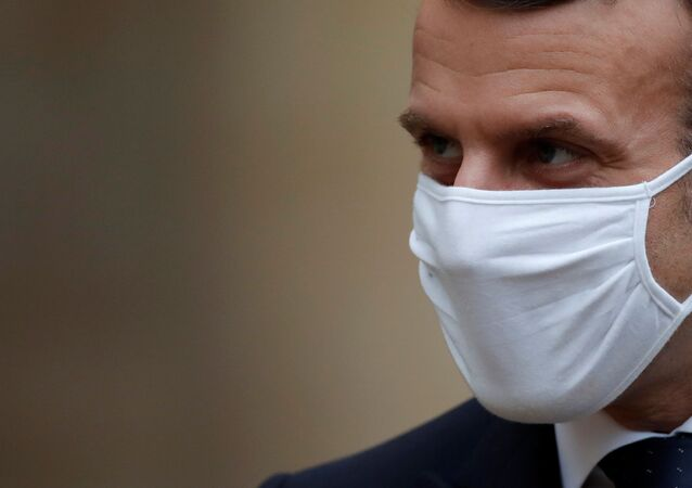 French President Emmanuel Macron, wearing a protective face mask, accompanies Interim Malian President Bah Ndaw (not seen) after a meeting at the Elysee Palace in Paris, France, January 27, 2021. REUTERS/Gonzalo Fuentes