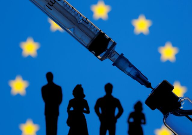 A vial, syringe and small toy figures are seen in front of a displayed EU flag in this illustration, taken 11 January 2021.