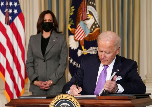 U.S. Vice President Kamala Harris watches as President Joe Biden signs executive orders on his racial equity agenda at the White House in Washington, U.S., January 26, 2021