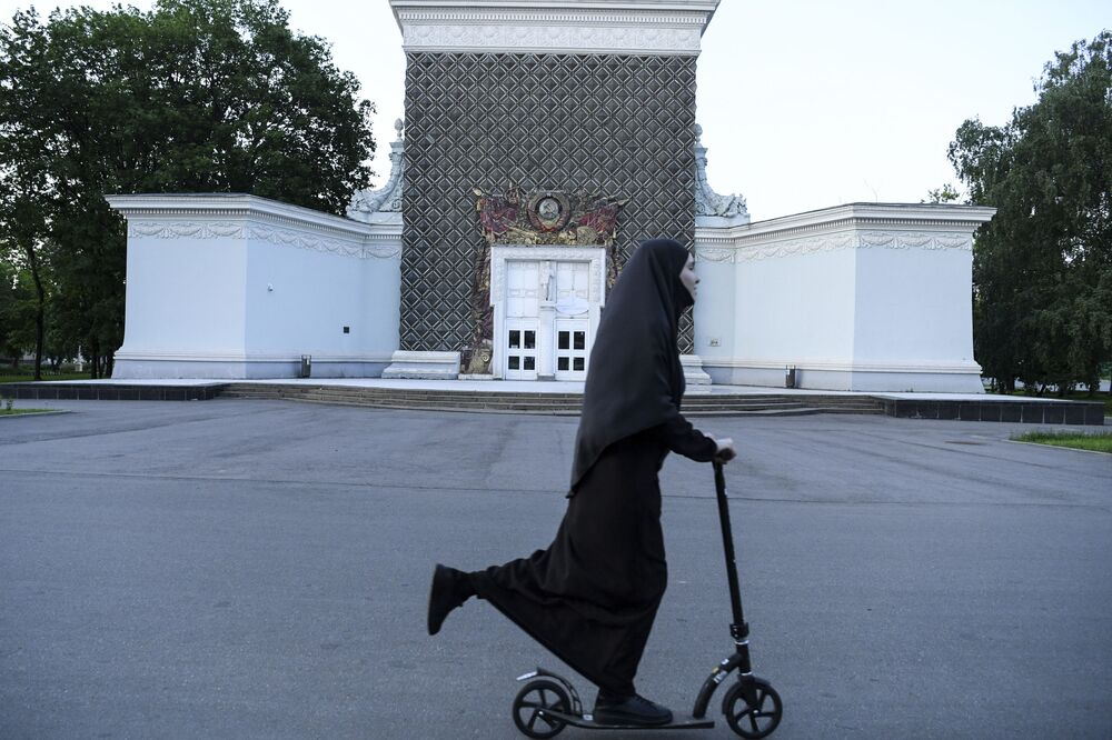 A woman wearing a hijab rides a scooter in Moscow on 14 June 2020.