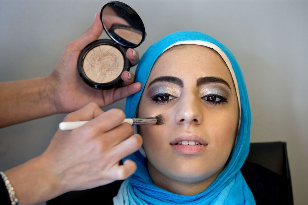 Hannah Shraim, 17, has her makeup done by Farah Kuriashi as she prepares to attend Northwest High School's senior prom, in Germantown, Md., Friday, 13 May 2016.