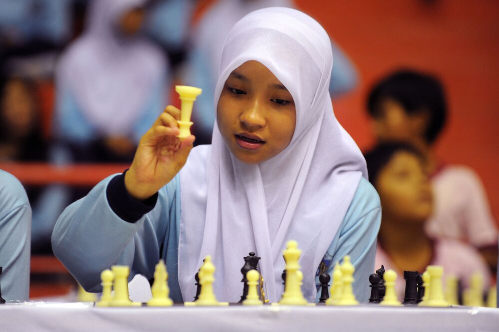 A girl in hijab plays chess at a Jakarta gymnasium, 23 September 2010.