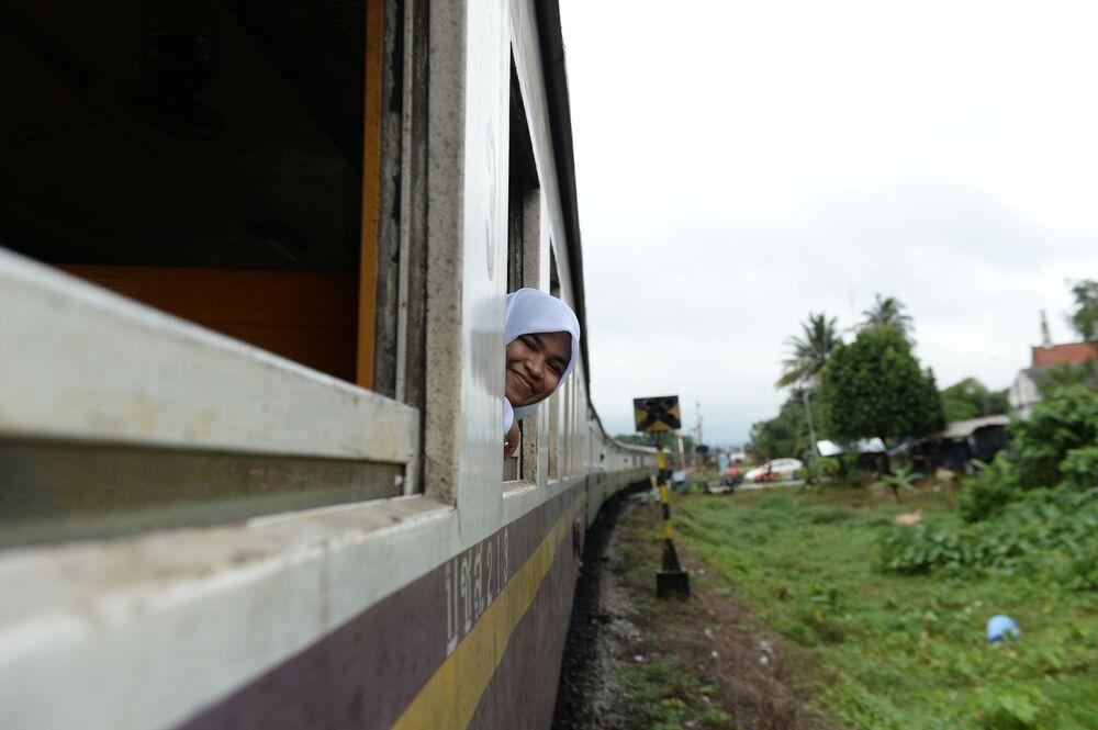A female Muslim student wearing hijab on a train