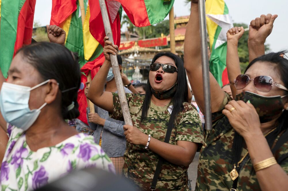 Supporters of Myanmar's military hold national flags as they take part in a protest against the Union Election Commission in Yangon, Myanmar, 29 January 2021.