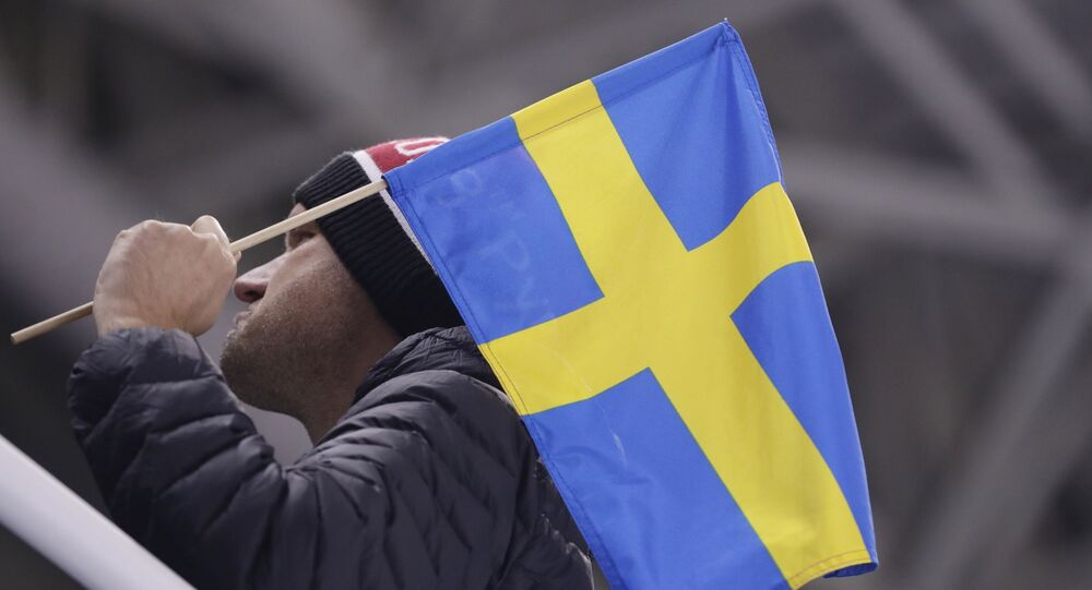 A man poses with a Swedish flag before the preliminary round of the men's hockey game between Sweden and Finland at the 2018 Winter Olympics in Gangneung, South Korea, Sunday, Feb. 18, 2018