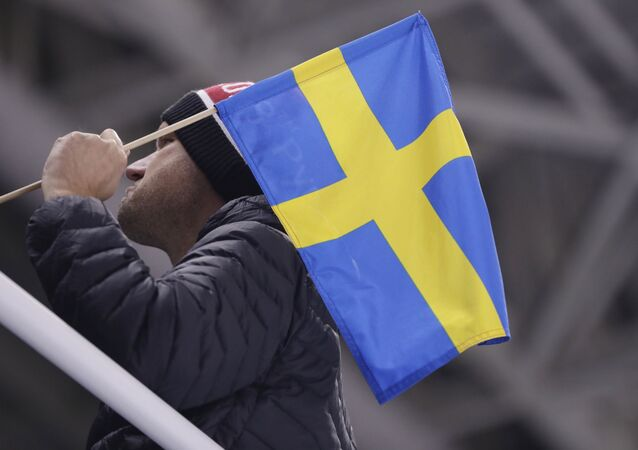 A man poses with a Swedish flag before the preliminary round of the men's hockey game between Sweden and Finland at the 2018 Winter Olympics in Gangneung, South Korea, 18 February 2018
