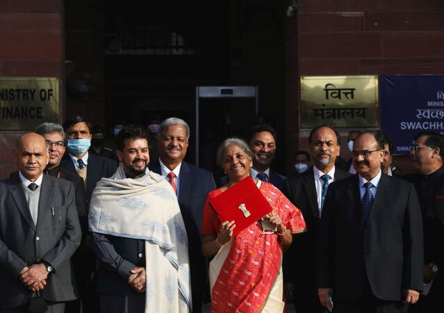 India's Finance Minister Nirmala Sitharaman holds up a folder with the Government of India logo, as India's Chief Economic Advisor Krishnamurthy Subramanian and Minister of State for Finance and Corporate Affairs Anurag Thakur look on as she leaves her office to present the federal budget in the parliament in New Delhi