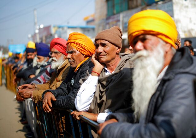 Farmers listen to a speaker during a protest against the farm laws at Singhu border near New Delhi