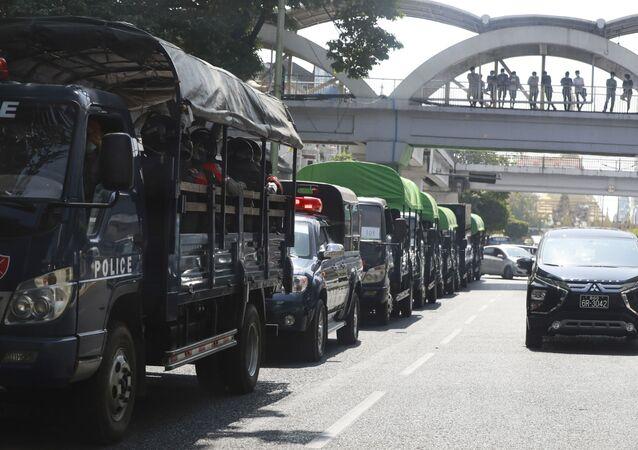 Policemen sit inside trucks parked on a road in the downtown area of Yangon, Myanmar