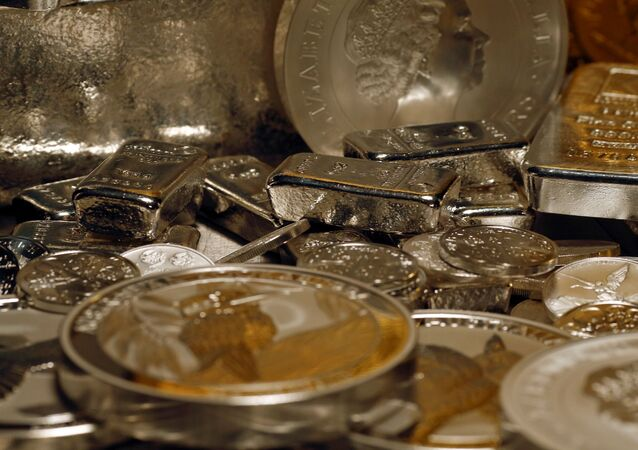 Silver bars and coins are stacked  on a table in the safe deposit boxes room of the ProAurum gold house in Munich, 3 March 2014.