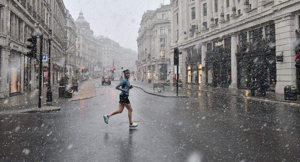 A jogger taking his daily exercise, crosses Regent Street in London in the snow on January 24, 2021, as the capital experiences a rare covering of snow on Sunday.