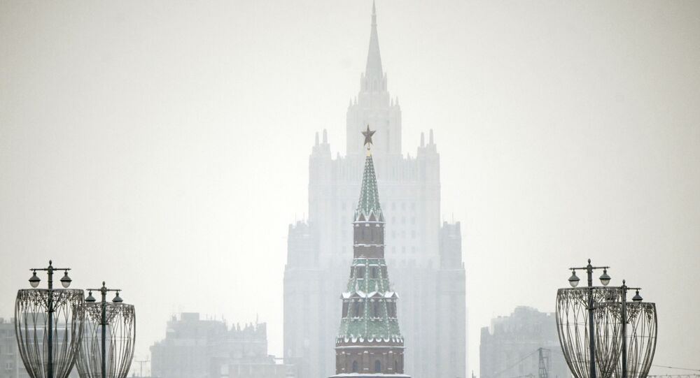 A man walks along a bridge in front of a Kremlin tower and the Russian Foreign Ministry building on the background in downtown Moscow on January 12, 2021.