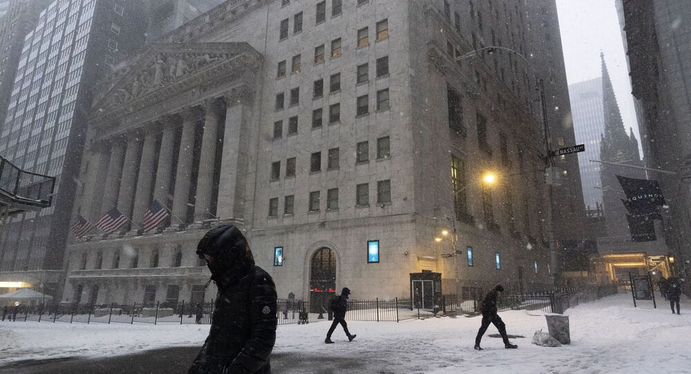 People walk past the New York Stock Exchange during a snowstorm, Monday, Feb. 1, 2021, in New York.