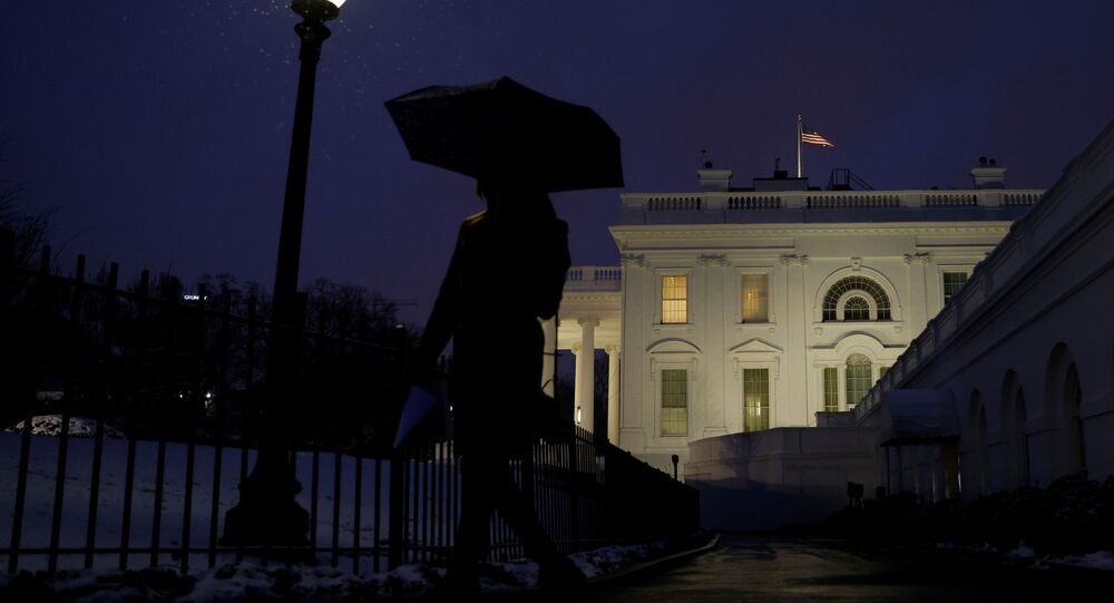 A staff member walks while holding an umbrella under snowfall at the White House in Washington, U.S., February 1, 2021.